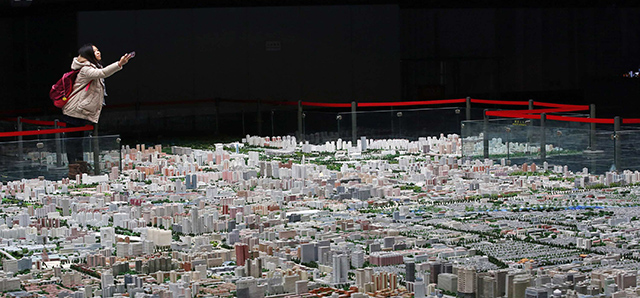 File photo of a visitor taking pictures of a model of Beijing's downtowns at the Beijing Planning Exhibition Hall